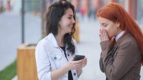 Dos mujeres de negocios atractivas jóvenes, pelirrojo y moreno, hablando y realizando acciones en smartphone almacen de metraje de vídeo