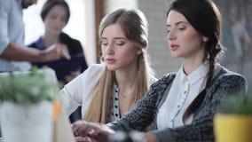 Dos mujeres de negocios atractivas jovenes trabajan en los ordenadores portátiles y discuten importante empiezan para arriba proy metrajes