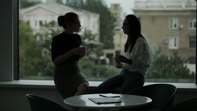 Dos mujeres de negocios cerca de la ventana en el café de consumición de la oficina al final del día y charla al chisme caliente almacen de video