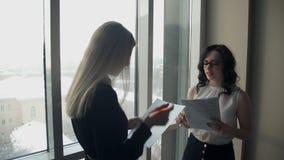 Dos mujeres de negocios contra ventana en pasillo discuten temas almacen de video