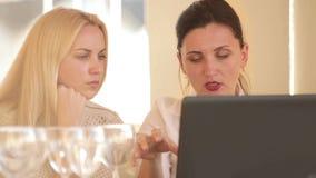 Dos mujeres de negocios de los compañeros de trabajo que discuten sus ideas del restaurante usando el ordenador portátil almacen de video