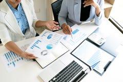Dos mujeres de negocios del líder que discuten las cartas y los gráficos que muestran los resultados fotografía de archivo