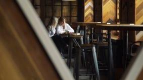 Dos mujeres de negocios en la reunión informal en café almacen de metraje de vídeo