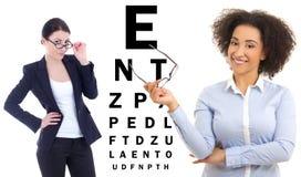 Dos mujeres de negocios en vidrios y la carta de prueba del ojo aislada en whi Imágenes de archivo libres de regalías