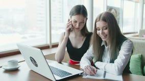 Dos mujeres de negocios hablan del trabajo en café almacen de metraje de vídeo