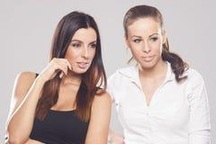 Dos mujeres de negocios hermosas en fondo del estudio Imagen de archivo
