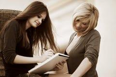 Dos mujeres de negocios jovenes de moda con el cuaderno Fotografía de archivo libre de regalías