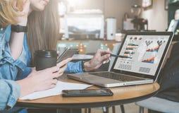 Dos mujeres de negocios jovenes que se sientan en la tabla en café, café de consumición y hablar Primera pluma y smartphone de te imagen de archivo