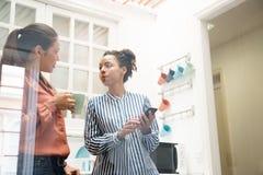 Dos mujeres de negocios que hablan en una cocina de la oficina Fotografía de archivo libre de regalías