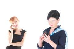 Dos mujeres de negocios que hablan por los teléfonos celulares Imágenes de archivo libres de regalías