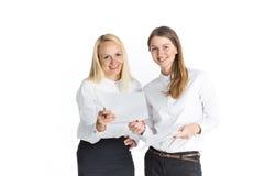 Dos mujeres de negocios que hablan y que firman el documento Fotos de archivo