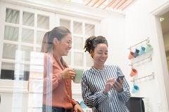 Dos mujeres de negocios que ríen en una cocina de la oficina Fotografía de archivo libre de regalías