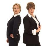 Dos mujeres de negocios que se colocan de nuevo a la parte posterior Imágenes de archivo libres de regalías