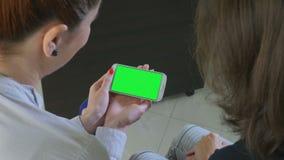 Dos mujeres de negocios que sostienen un smartphone con la pantalla verde metrajes