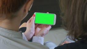 Dos mujeres de negocios que sostienen un smartphone con la pantalla verde almacen de metraje de vídeo