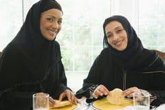 Dos mujeres de Oriente Medio que disfrutan de una comida fotos de archivo libres de regalías