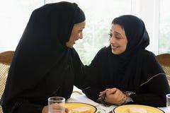 Dos mujeres de Oriente Medio que disfrutan de una comida foto de archivo libre de regalías