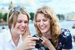 Dos mujeres de risa de la belleza que miran la pantalla de la cámara Foto de archivo libre de regalías