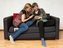 Dos mujeres de Yong con los teléfonos móviles Foto de archivo libre de regalías