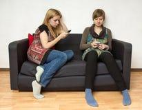 Dos mujeres de Yong con los teléfonos móviles Imagenes de archivo