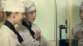 Dos mujeres del cocinero que se divierten en una cocina metrajes