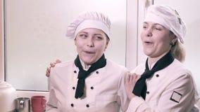 Dos mujeres del cocinero que se divierten en una cocina almacen de metraje de vídeo