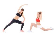 Dos mujeres deportivas delgadas que hacen estirando los ejercicios aislados en whi Fotografía de archivo libre de regalías