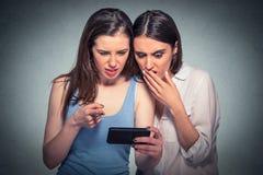 Dos mujeres descontentadas que miran el teléfono móvil Foto de archivo