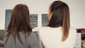Dos mujeres discuten el menú y eligen la comida en una situación del café en el contador de la barra almacen de video