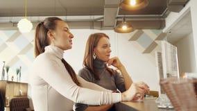 Dos mujeres discuten el menú y eligen la comida en una situación del café en el contador de la barra metrajes