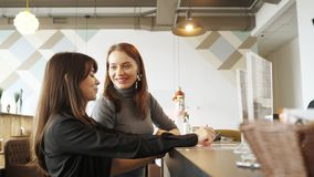 Dos mujeres discuten el menú y eligen la comida en una situación del café en el contador de la barra almacen de metraje de vídeo