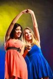 Dos mujeres divertidas que llevan a cabo las manos en vestidos Imagen de archivo libre de regalías