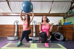 Dos mujeres ejercitan la estocada de la pierna de la bola una de la estabilidad de los pesos de pasos Imagenes de archivo