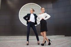 Dos mujeres elegantes que presentan contra de la pared del edificio Foto de archivo libre de regalías