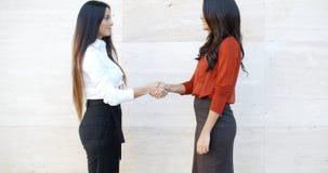 Dos mujeres elegantes que sacuden las manos al aire libre imagenes de archivo