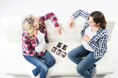 Dos mujeres embarazadas atractivas que miran las fotos del ultrasonido Imágenes de archivo libres de regalías