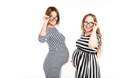 Dos mujeres embarazadas felices son vidrios tocan su vientre Foto de archivo libre de regalías