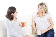 Dos mujeres embarazadas hermosas con el jugo de zanahoria Fotos de archivo libres de regalías