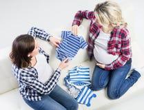 Dos mujeres embarazadas hermosas jovenes en un sofá Fotografía de archivo