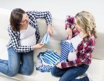 Dos mujeres embarazadas que comprueban hacia fuera el desgaste de los niños Foto de archivo libre de regalías