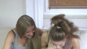 Dos mujeres emocionadas hermosas que usan la PC de la tableta en la sala de estar metrajes