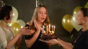 Dos mujeres en casquillos que cantan la canción del feliz cumpleaños a su amigo y que dan una torta de chocolate Señora asombrosa metrajes