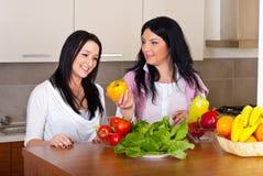 Dos mujeres en cocina con las verduras frescas Fotos de archivo libres de regalías