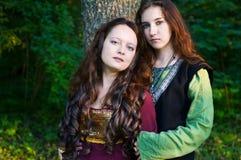 Dos mujeres en el abrazo medieval de las alineadas Foto de archivo