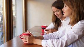 Dos mujeres en el café que hablan, usando smartphone y la tableta almacen de metraje de vídeo