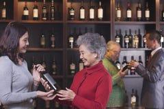 Dos mujeres en el primero plano que compran y que discuten el vino, dos hombres en el fondo Foto de archivo libre de regalías