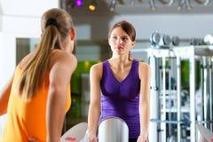 Dos mujeres en gimnasia delante de una máquina de ejercicio Foto de archivo libre de regalías