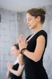 Dos mujeres en gimnasio clasifican, ejercicio de la relajación o clase de la yoga fotos de archivo libres de regalías