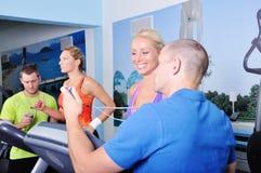 Dos mujeres en gimnasio que ejercitan con el instructor personal de la aptitud Imágenes de archivo libres de regalías