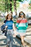 Dos mujeres en la ciudad que caminan junto - a la mujer con huecos del color en el vestido imagenes de archivo
